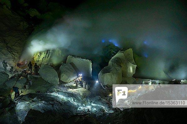 Arbeiter bei giftigem Schwefelabbau in Schwefelmine bei Nacht  hinten blaues Feuer des Vulkans Ijen  Ijen  Java  Indonesien  Asien