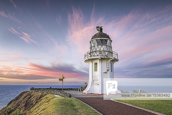 Leuchtturm mit Wegweiser am Cape Reinga bei Abendrot mit rosa Wolken  Far North District  Northland  Nordinsel  Neuseeland  Ozeanien