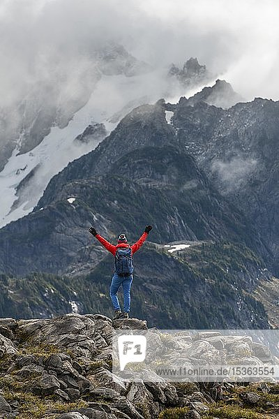 Female hiker stretches arms into the air  view of Mt. Shuksan with snow and glacier  cloudy sky  Mt. Baker-Snoqualmie National Forest  Washington  USA  North America
