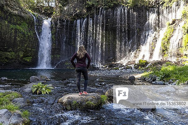 Junge Frau steht auf einem Stein in einem Fluss  Shiraito Wasserfall  Präfektur Yamanashi  Japan  Asien