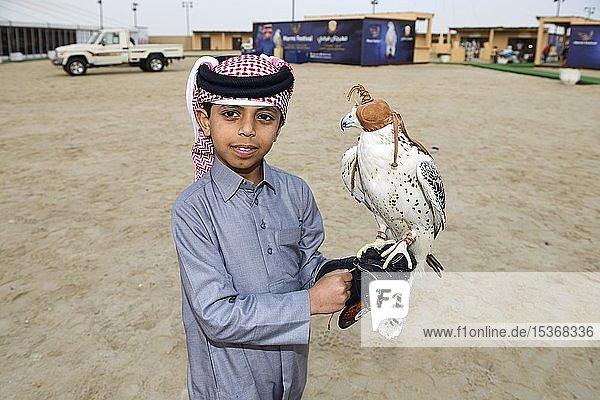 Qatari Junge mit Falke beim Marmi Falcon-Festival  Sealine Dunes  Mesaieed  Doha  Qatar