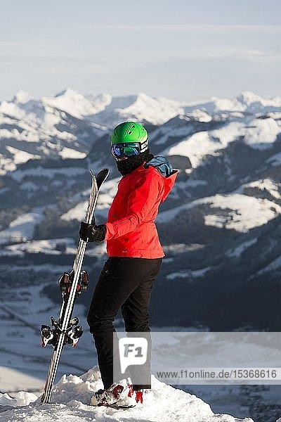 Skifahrerin mit Skihelm steht mit Ski an der Skipiste über dem Tal  blickt in die Kamera  hinten Berge  SkiWelt Wilder Kaiser  Brixen im Thale  Tirol  Österreich  Europa