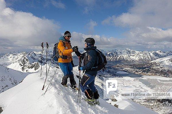 Bergsteiger gratulieren sich am Gipfel des Stortinden im Winter  Svolvaer  Austvågøy  Lofoten  Norwegen  Europa