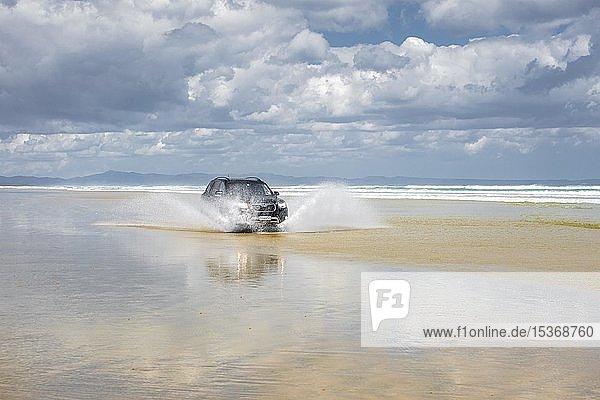 Schwarzer Hyundai Santa Fe 4x4 Geländewagen fährt am Sandstrand des Ninety Mile Beach im Wasser  Far North District  Northland  Nordinsel  Neuseeland  Ozeanien