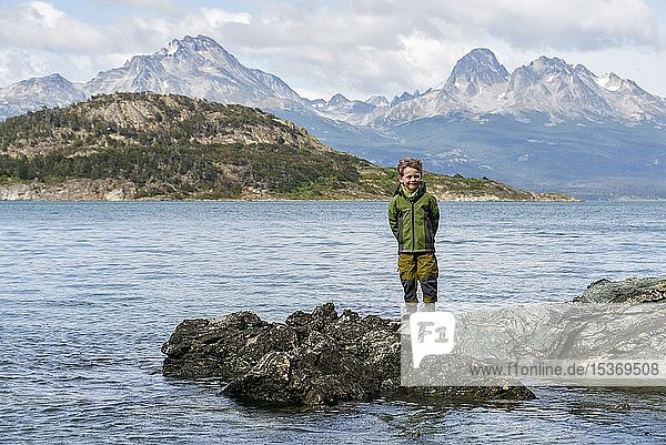 Little boy standing on rocks on the banks of the Beagle Channel  Fin del Mundo  end of the world  Parque Nacional Tierra del Fuego National Park  Andes  Tierra del Fuego  Argentina  South America
