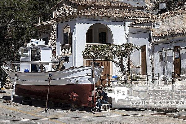 Einheimischer Mann repariert ein Fischerboot im Hafen von Cala Figuera  Mallorca  Balearen  Spanien  Europa