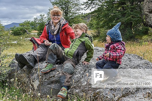 Mother with two small children sitting at a rest while hiking on rocks  Patagonia  Chile  South America