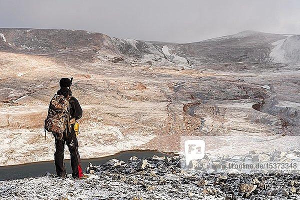 Touristenführer mit Gewehr hält Ausschau nach Eisbären  Snaddvika  Nordaustland  Spitzbergen Inselgruppe  Svalbard und Jan Mayen  Norwegen  Europa
