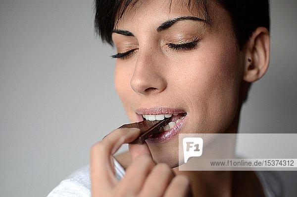 Junge Frau nascht Schokolade  Portrait  Spanien  Europa