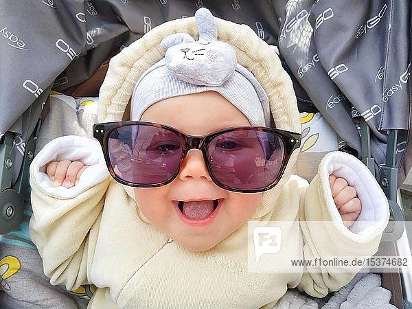 Lustiges Gesicht eines Babys  glückliches Mädchen mit Sonnenbrille lacht  Ukraine  Europa