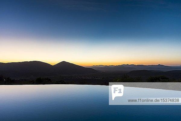 Swimmingpool mit wunderschöner Aussicht und Berg bei Sonnenuntergang  Opuvo  Kaokoland  Namibia  Afrika