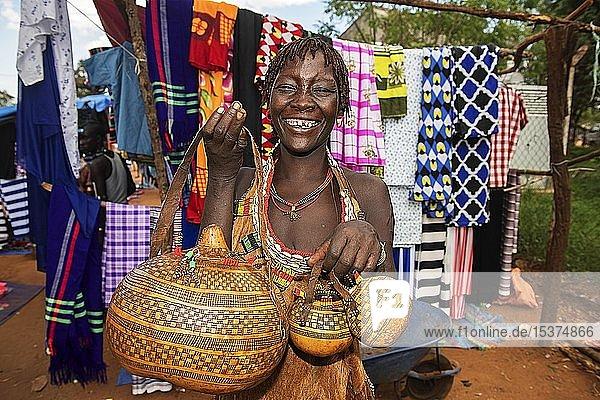 Lachende Frau der Volksgruppe der Hamer verkauft kunstvoll verzierte Kallebassen-Kürbisse  Markt in Dimeka  Unteres Omo-Tal  Omo-Region  Süd-Äthiopien  Äthiopien  Afrika