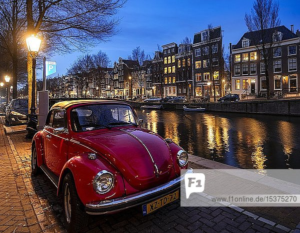 Alter VW Käfer parkt am Kanal  historische Häuserzeile an einer Gracht bei Abenddämmerung  Amsterdam  Nordholland  Niederlande  Europa
