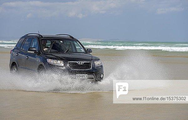 Schwarzer Hyundai Santa Fe 4x4 Geländewagen fährt am Sandstrand des Ninety Mile Beach im Wasser,  Far North District,  Northland,  Nordinsel,  Neuseeland,  Ozeanien