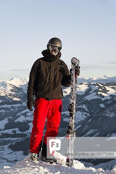 Skifahrer steht an der Piste und hält Ski  Blick in die Kamera  Gipfel Hohe Salve  SkiWelt Wilder Kaiser Brixenthal  Hochbrixen  Tirol  Österreich  Europa