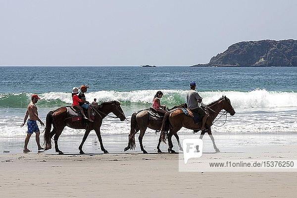 Reiter auf Pferden am Strand Playa Espadilla  Manuel Antonio Nationalpark  Provinz Puntarenas  Costa Rica  Mittelamerika