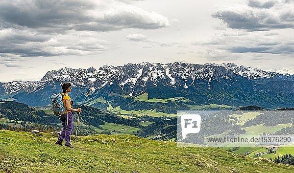 Wanderin auf dem Wanderweg zum Spitzstein  hinten Bergkette Zahmer Kaiser mit Schnee  Erl  Österreich  Europa