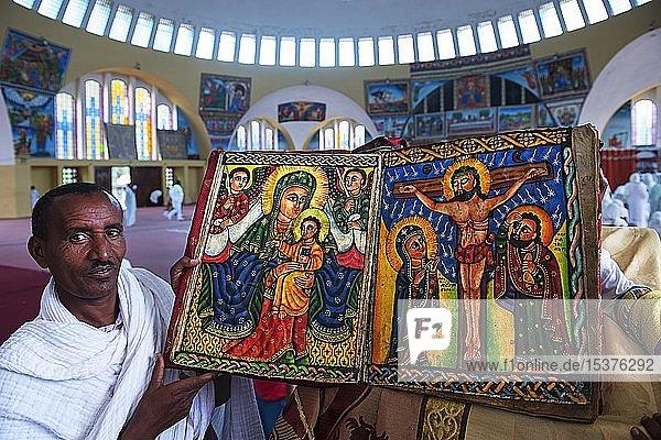 Priester zeigt handgemalte Bibel mit der Maria und Jesus und Kreuzigung Jesus  Marienkirche  Axum  Äthiopien  Afrika Priester zeigt handgemalte Bibel mit der Maria und Jesus und Kreuzigung Jesus, Marienkirche, Axum, Äthiopien, Afrika