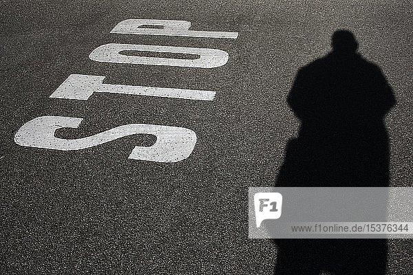 Fahrbahnmarkierung  Bodenmarkierung  STOP-Hinweis auf Asphalt  Personen-Schatten