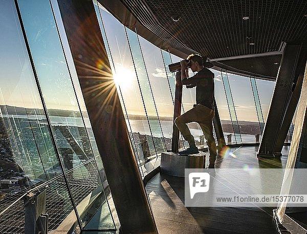 Tourist schaut durch Fernglas  Aussichtsplattform des Sky Tower  Central Business District  Auckland  Nordinsel  Neuseeland  Ozeanien