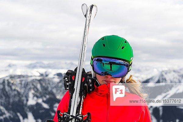 Skifahrerin mit Skihelm  Skibrille und Ski blickt in die Kamera  Portrait  hinten Berge  SkiWelt Wilder Kaiser  Brixen im Thale  Tirol  Österreich  Europa