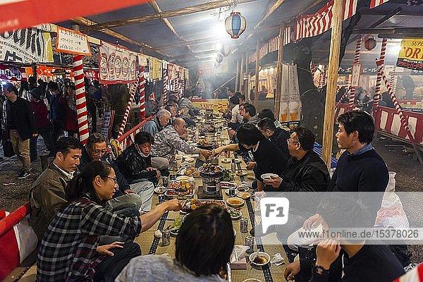 Kirschblütenfest  Hanami  Japaner essen an einer langen Tafel  Abendstimmung  Hirano Schrein  Kyoto  Japan  Asien