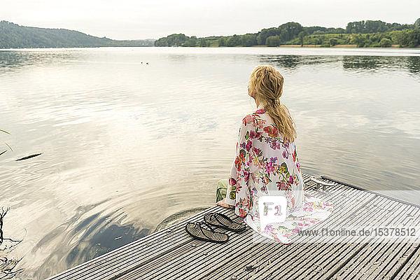 Junge Frau sitzt auf einem Steg an einem See