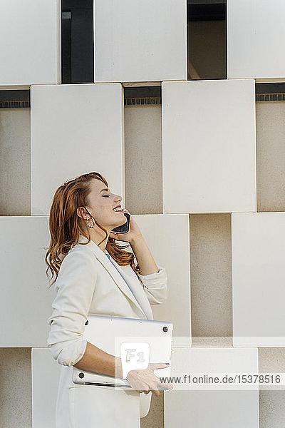 Geschäftsfrau in weißem Hosenanzug  mit Laptop  telefoniert