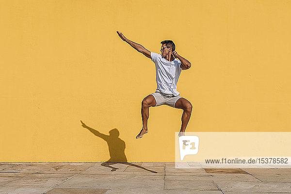 Junger Mann springt vor eine gelbe Mauer