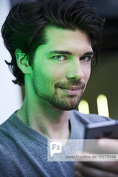 Nahaufnahme eines selbstbewussten Mannes mit grünem Licht  der ein Mobiltelefon hält