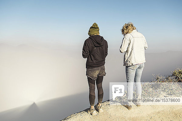 Young women with respirator masks standing at the edge of volcano Ijen  Java  Indonesia