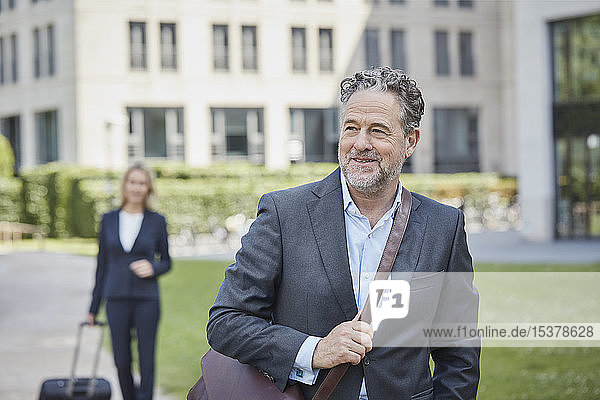 Porrait of smiling businessman in the city with businesswoman in background