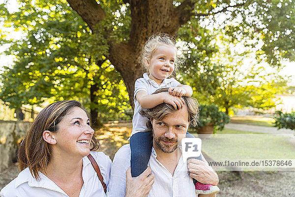 Glückliche Familie in einem Park mit einem Vater  der seine kleine Tochter auf den Schultern trägt