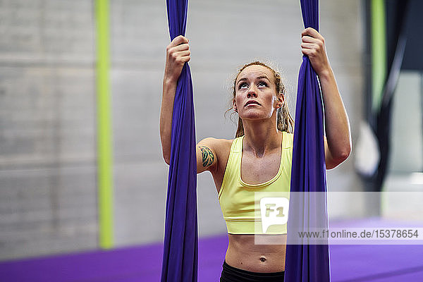 Young woman preparing for aerial silk in an exercise room