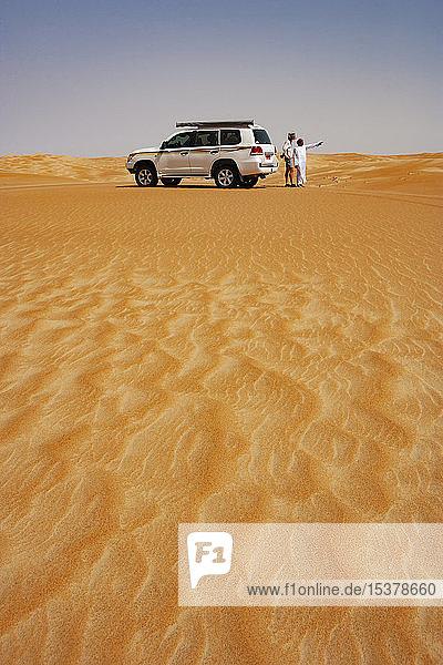Tourist im Gespräch mit seinem Fahrer in der Wüste neben dem Geländewagen  Wahiba Sands  Oman