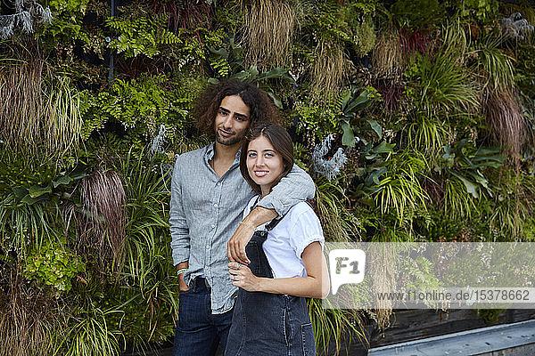 Porträt eines lächelnden jungen Paares vor einer Pflanzenwand