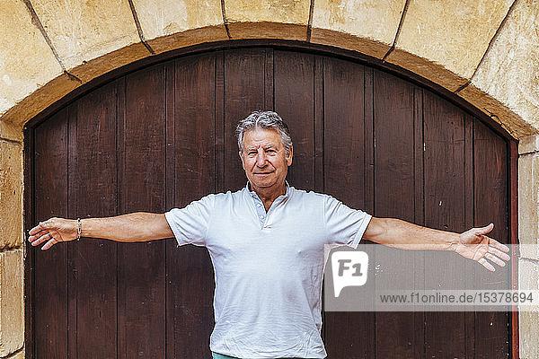 Porträt eines älteren Mannes vor einer Holztür