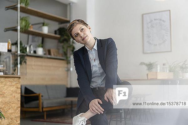 Porträt einer Geschäftsfrau  die in einem Cafe sitzt und wegschaut