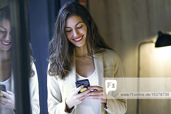 Smiling young businesswoman checking cell phone at the window