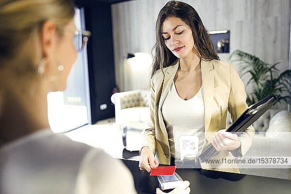 Businesswoman paying with contactless credit card at reception