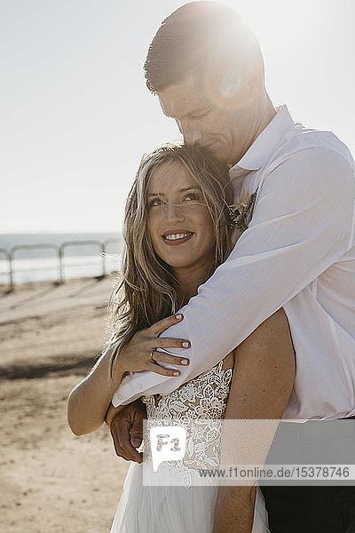 Liebevolle Umarmung von Braut und Bräutigam am Strand bei Sonnenuntergang