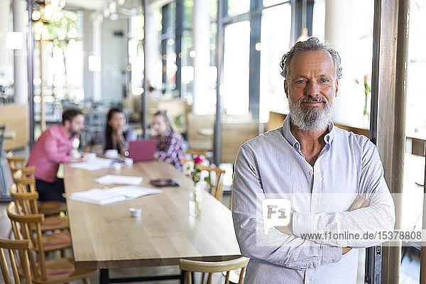 Porträt eines reifen Geschäftsmannes in einem Cafe mit Kollegen  die im Hintergrund eine Besprechung abhalten