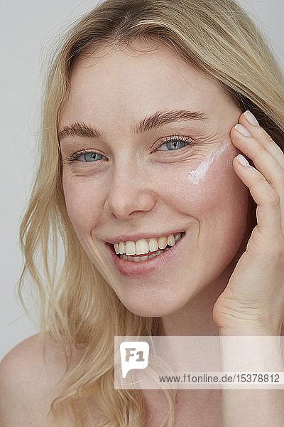 Porträt einer lächelnden jungen Frau  die ihr Gesicht eincremt