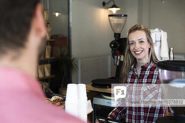 Lächelnde Frau am Tresen eines Cafés,  die den Mann ansieht
