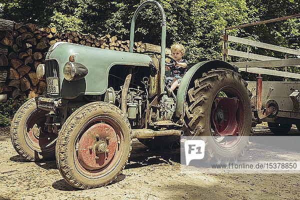 Kleiner Junge,  der vorgibt,  einen Traktor zu fahren