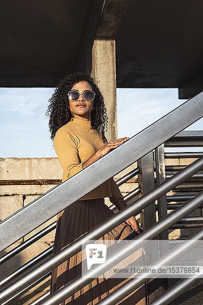 Schöne Frau  trägt Sonnenbrille  steht auf einer Treppe Schöne Frau, trägt Sonnenbrille, steht auf einer Treppe