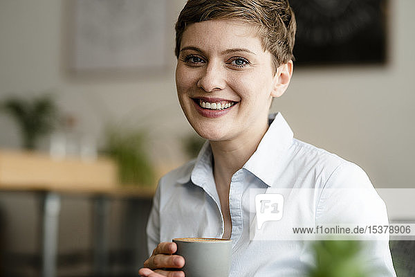 Porträt einer glücklichen Geschäftsfrau mit einer Tasse Kaffee