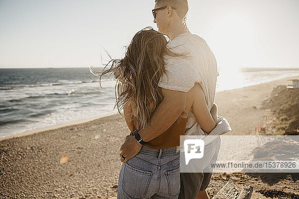 Affectionate young couple enjoying the view on the beach at sunset