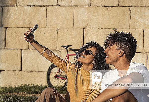 Junges Paar  das sich mit einem Smartphone selbstständig macht und vor der Wand sitzt Junges Paar, das sich mit einem Smartphone selbstständig macht und vor der Wand sitzt