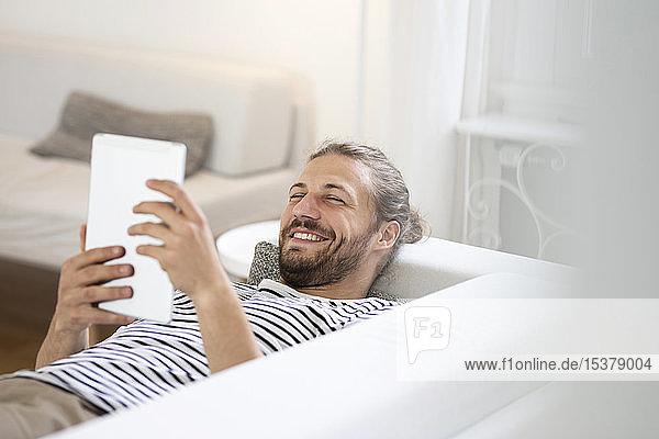 Lächelnder junger Mann liegt zu Hause auf Couch und benutzt Tablette